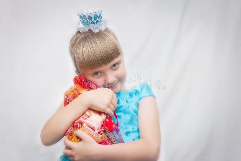 Молодая принцесса в голубом платье отжатом к его сумкам подарка Novogodniy комода конфеты Портрет ребенка стоковая фотография
