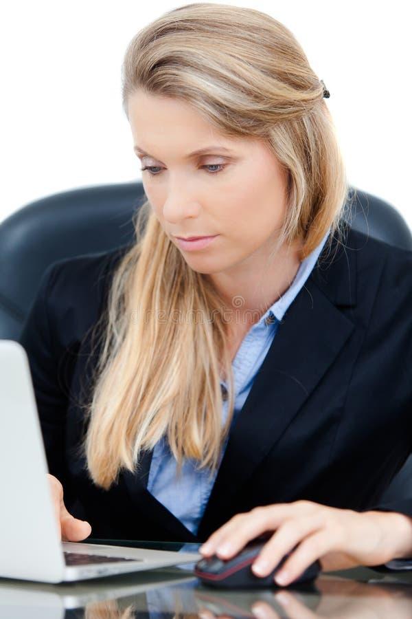 Молодая профессиональная бизнес-леди работая на столе стоковое изображение