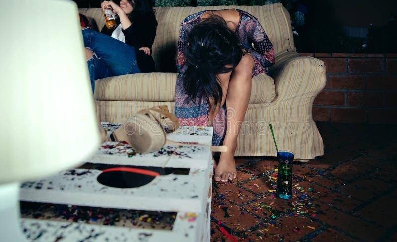 Молодая пьяная женщина сидя в софе на партии стоковое фото rf