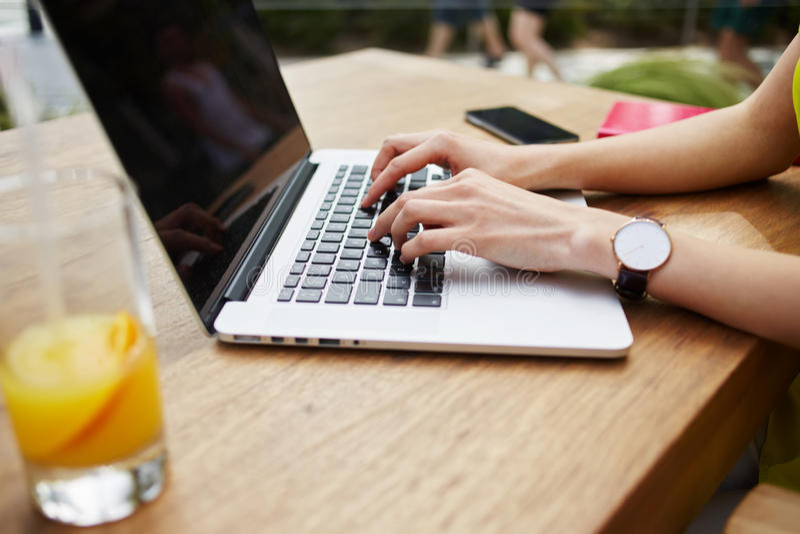 Молодая работа бизнес-леди на тексте netbook печатая во время завтрака в современной кофейне стоковые изображения rf