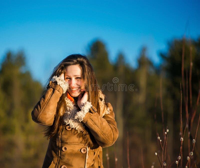 Молодая радостная славная белокурая женщина одела пальто и шарф овчины Девушка наслаждается теплым солнечным весенним днем и ее д стоковое изображение rf
