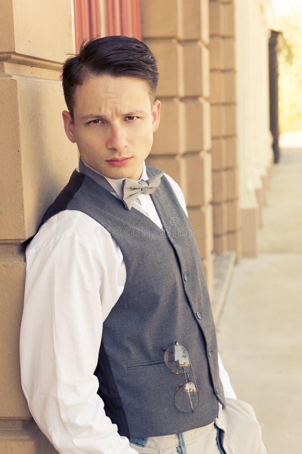 Молодая ретро мужская модель представляя outdoors стеной стоковое фото
