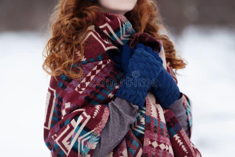 Молодая рыжеволосая женщина в голубых наушниках и перчатках стоковые фото