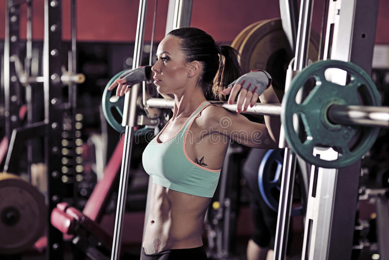 Молодая сексуальная девушка в спортзале делая сидение на корточках на красной предпосылке стоковая фотография rf