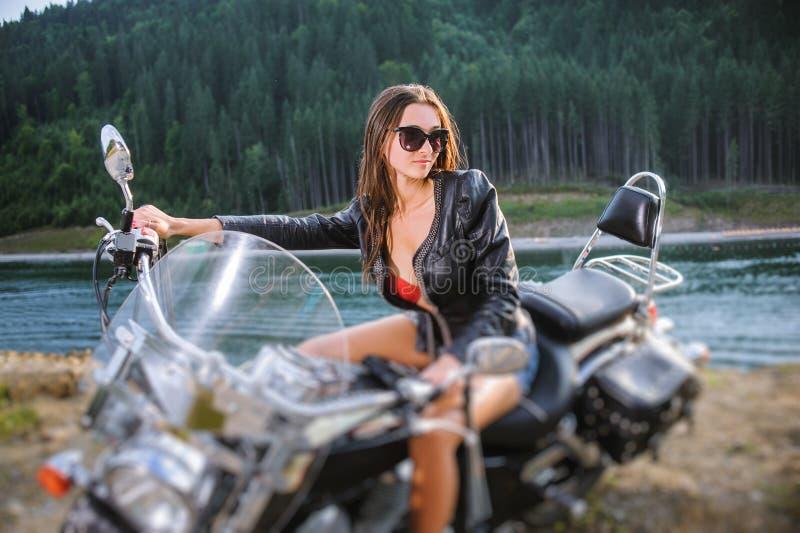 Молодая сексуальная девушка сидя на выполненном на заказ мотоцикле крейсера стоковые фотографии rf