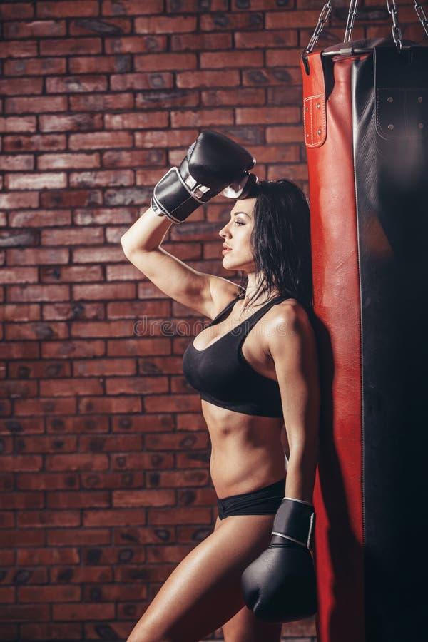 Молодая сексуальная девушка с перчатками бокса, груша стоковое фото rf