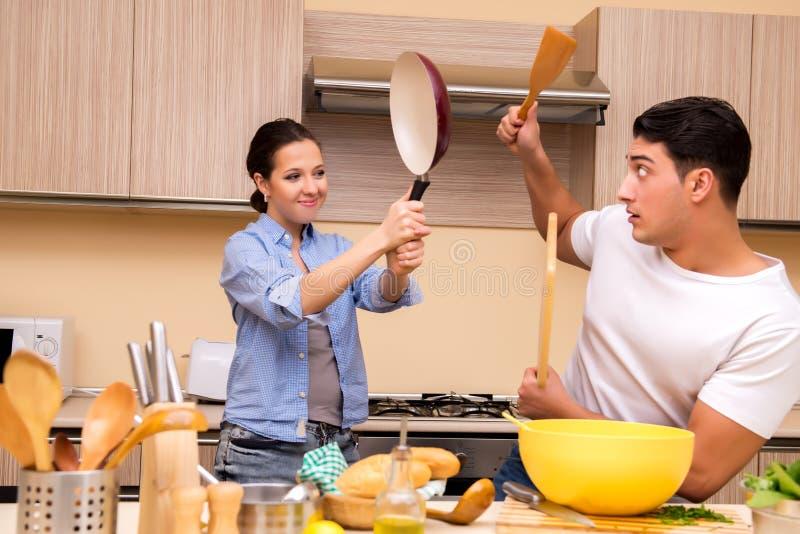 Молодая семья делая смешной бой на кухне стоковое изображение