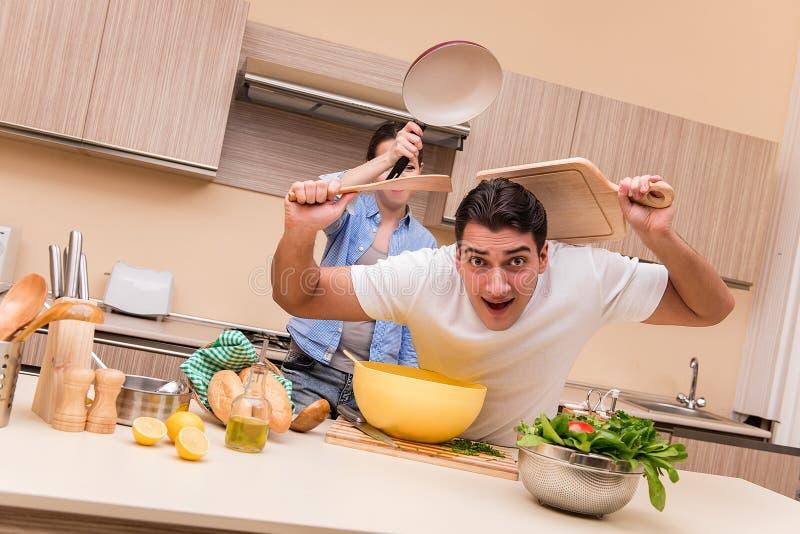 Молодая семья делая смешной бой на кухне стоковая фотография rf