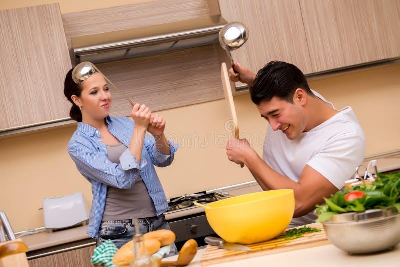 Молодая семья делая смешной бой на кухне стоковые фотографии rf