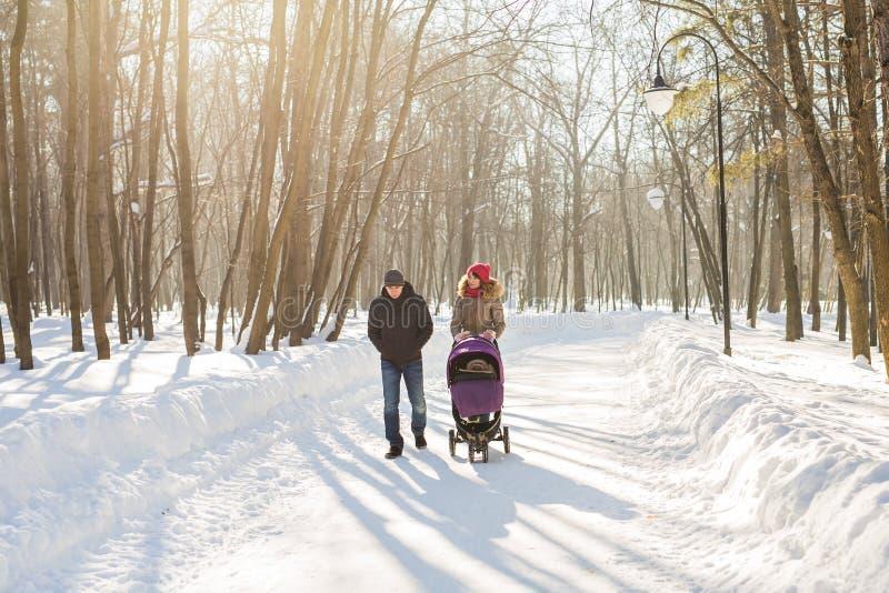 Молодая семья идя с детской сидячей коляской в парке стоковое изображение