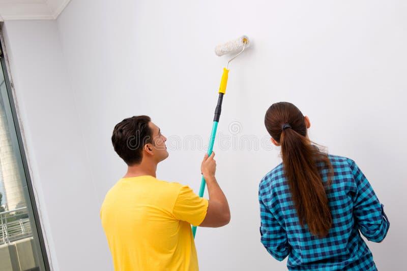 Молодая семья крася стены в diy концепции стоковое изображение rf