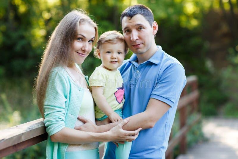 Молодая семья, мать, отец и маленькая дочь в парке стоковое фото rf