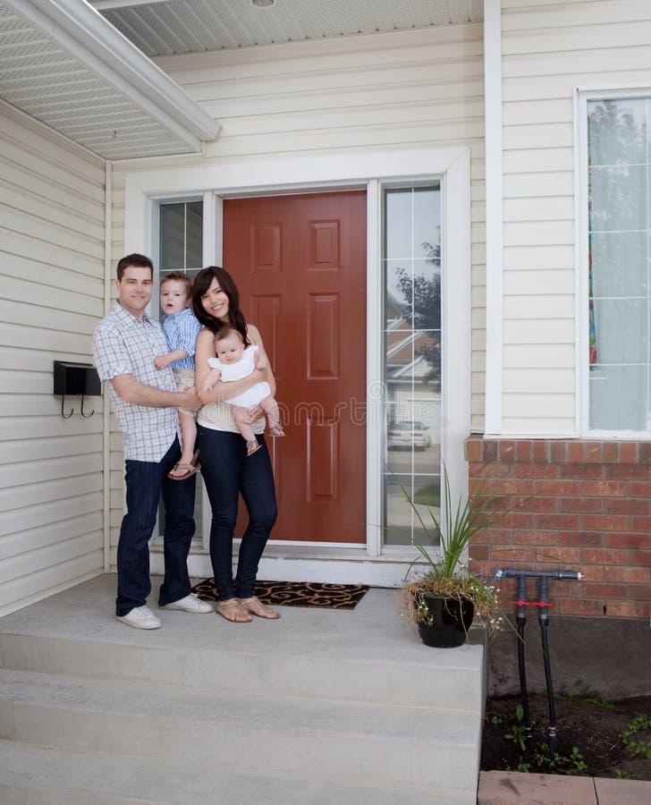 Молодая семья перед домом стоковое изображение rf