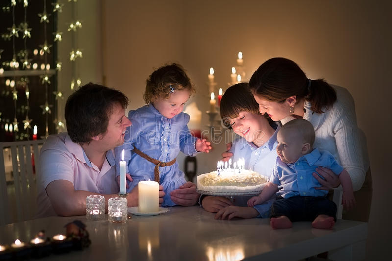 Молодая семья празднуя день рождения их сына стоковое изображение