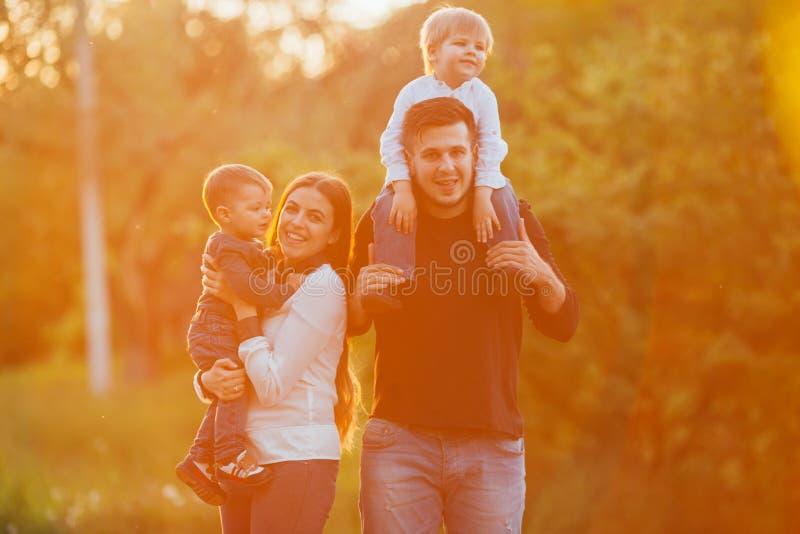Молодая семья при дети идя в парк Отец, мать и 2 сыновь стоковое фото rf