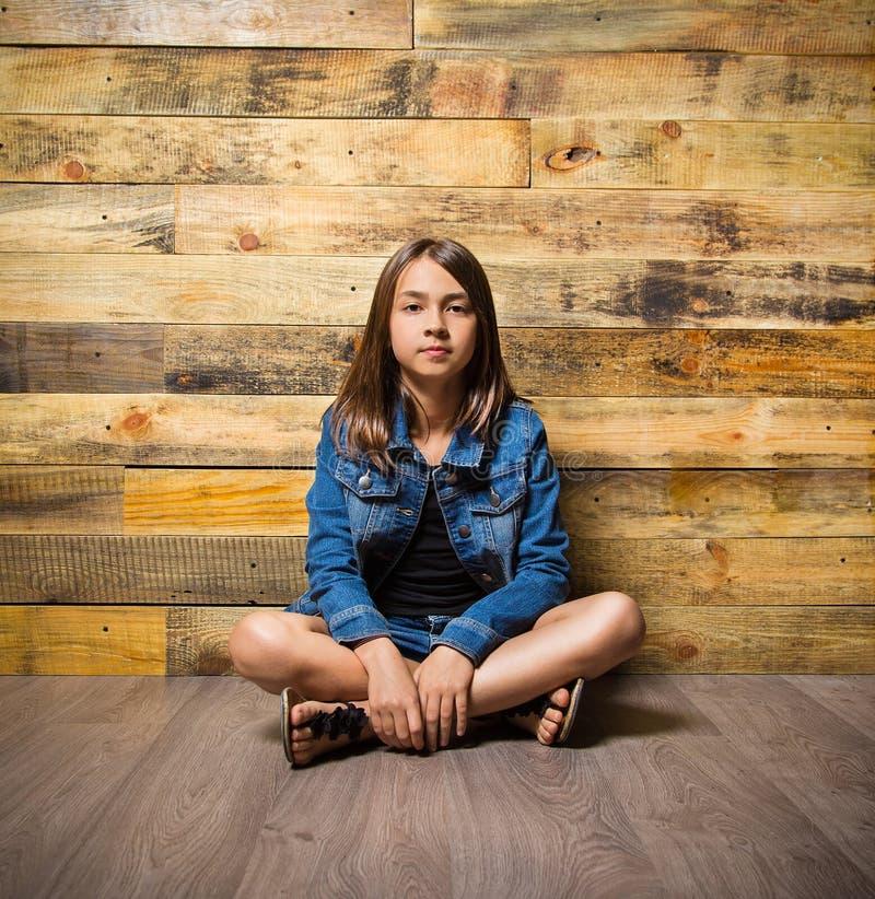 Молодая серьезная девушка сидя на поле стоковая фотография