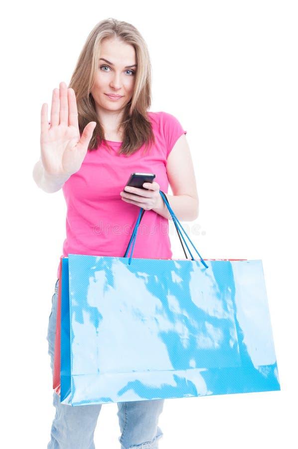 Молодая серьезная женщина на покупках делая знак стопа стоковое изображение