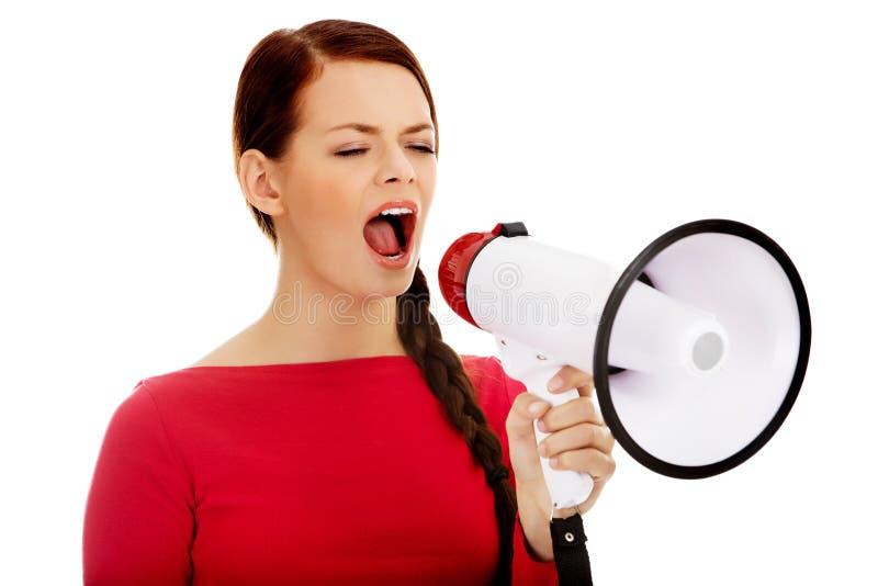 Молодая сердитая женщина кричащая через мегафон стоковое изображение
