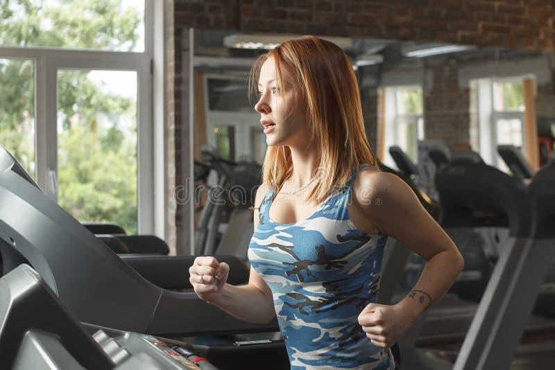 Молодая сильная девушка бежать на третбане в спортзале стоковые изображения rf