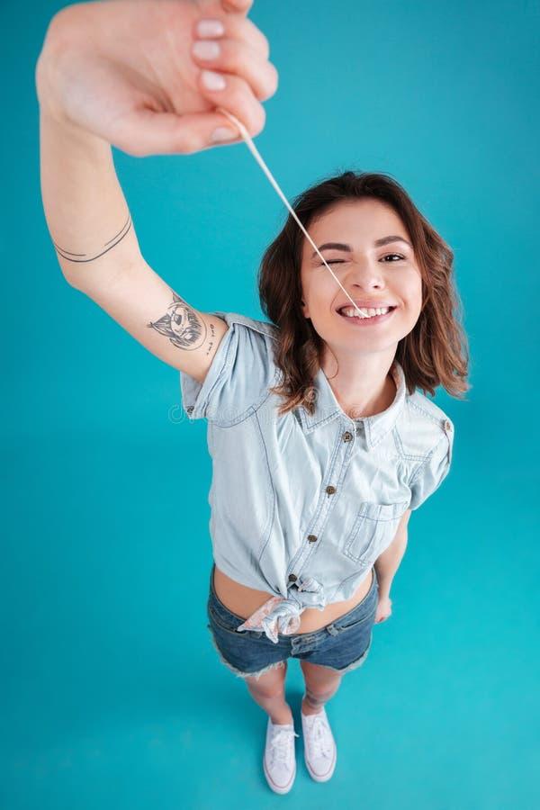 Молодая смешная предназначенная для подростков девушка протягивая и играя с buble камедью стоковая фотография