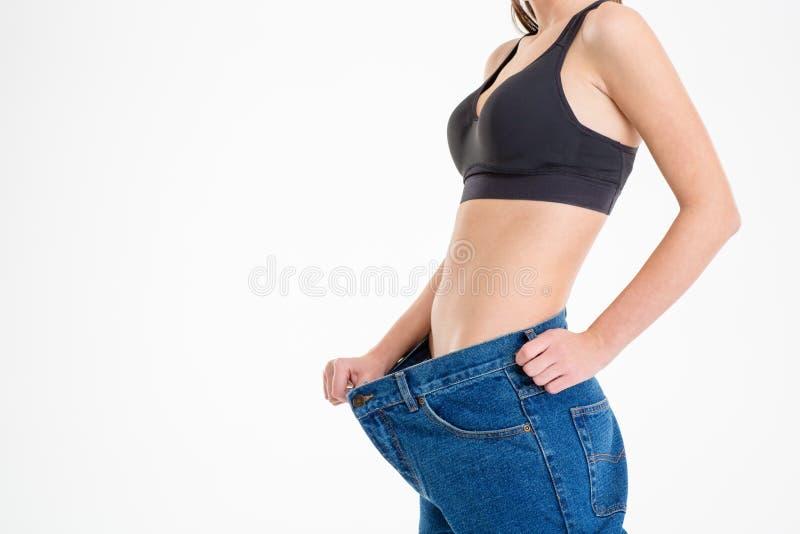 Молодая спортсменка с красивым телом в старых больших джинсах стоковые фото