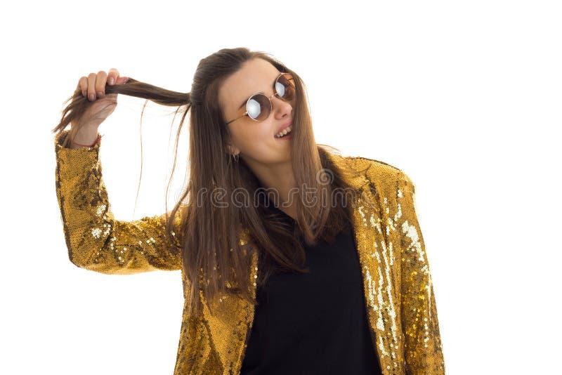 Молодая стильная женщина в золотых куртке и солнечных очках стоковые изображения rf