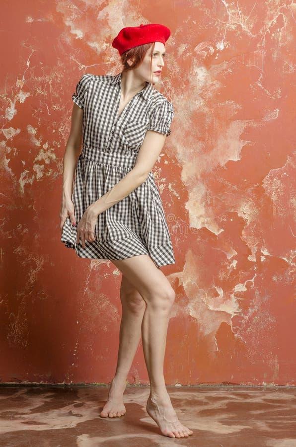 Молодая стильная женщина в стильном платье в винтажном стиле и красном берете стоковое фото rf