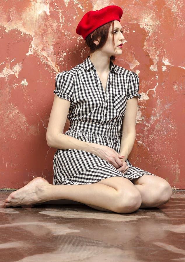 Молодая стильная женщина в стильном платье в винтажном стиле и красном берете стоковые фото