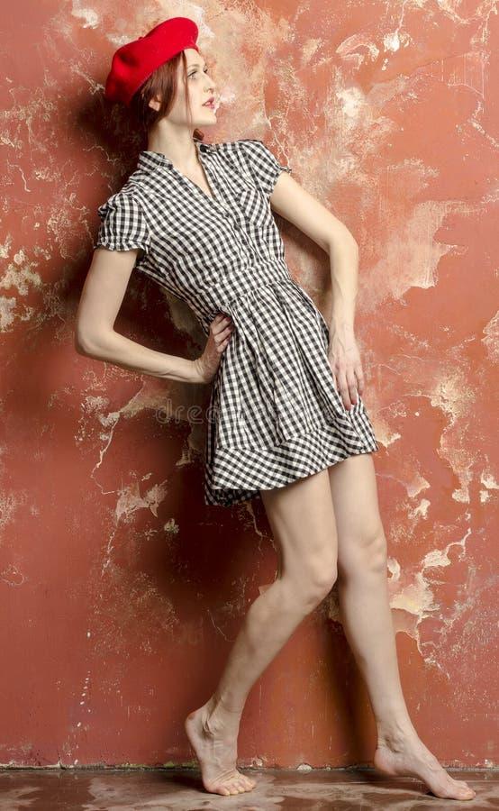 Молодая стильная женщина в стильном платье в винтажном стиле и красном берете стоковые изображения rf