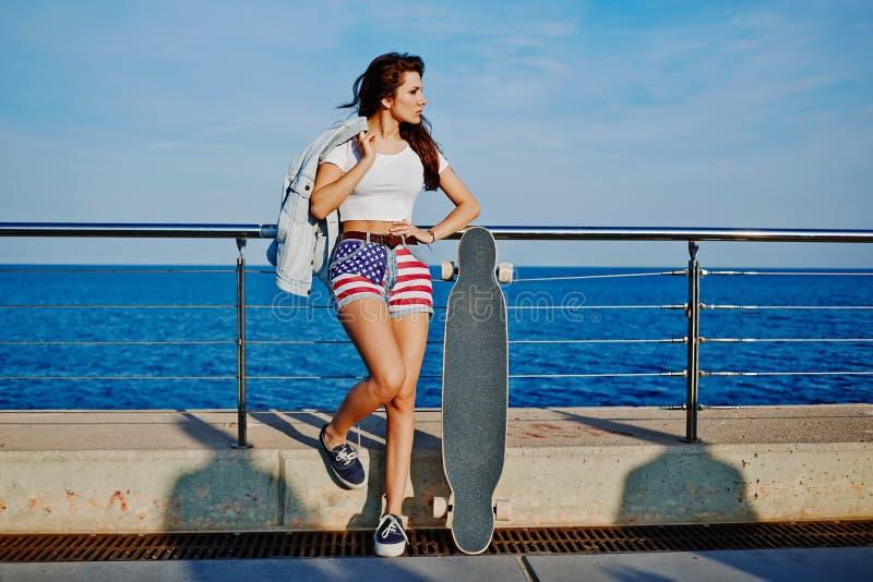 Молодая стильная женщина представляя outdoors в лете стоковое фото