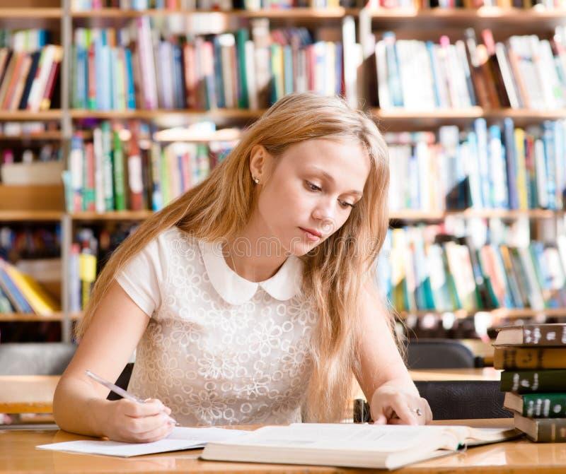 Молодая студентка делая назначения в библиотеке стоковая фотография rf