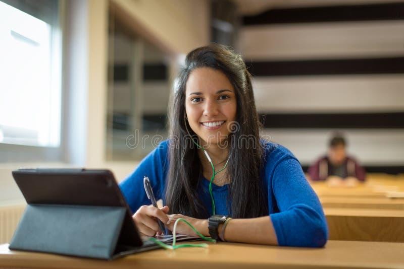 Молодая студентка на классе университета Она ` s используя таблетку и наушники для принимать примечания стоковое изображение