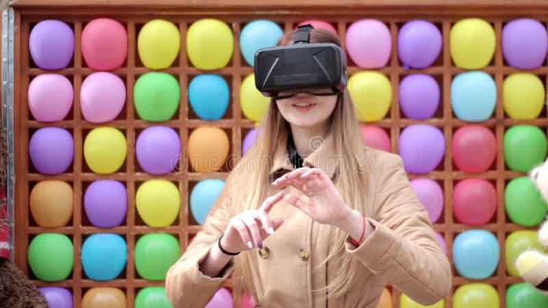 Молодая счастливая девушка на улице в бежевом пальто играя имеющ стекла шлемофона виртуальной реальности потехи нося, красочную п сток-видео