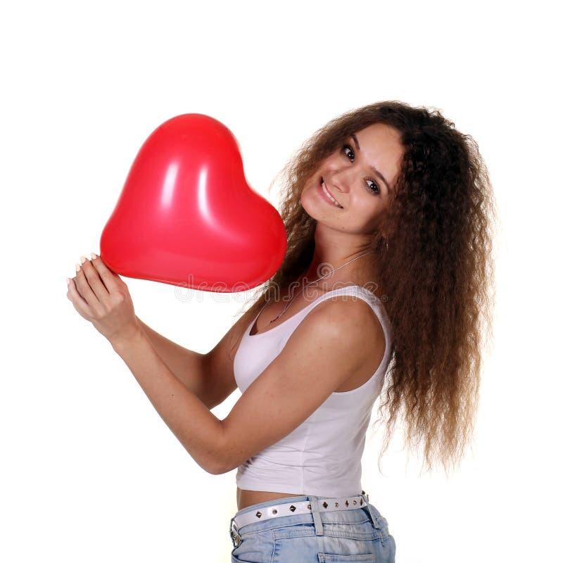 Молодая счастливая девушка с красным воздушным шаром стоковые фото