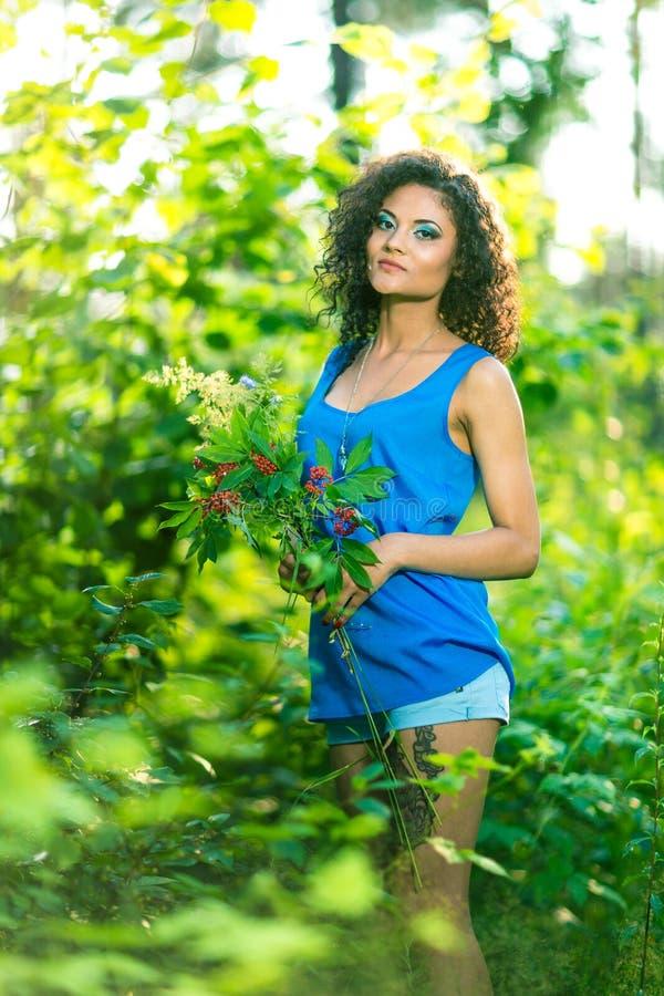 Молодая счастливая женщина держа большой букет весны цветет outdoors стоковая фотография