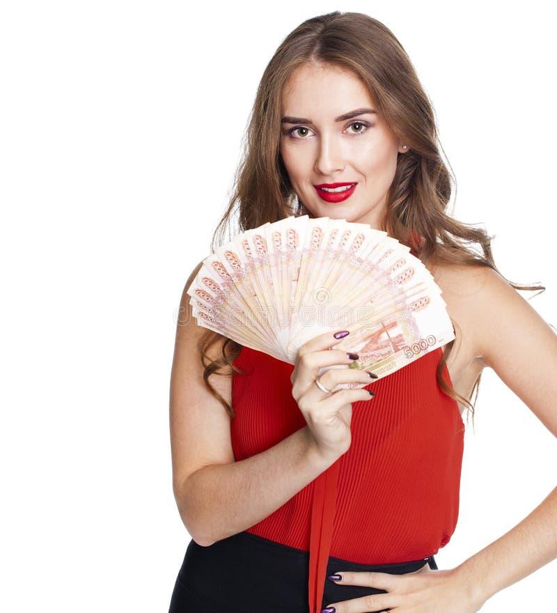 Молодая счастливая женщина держа вентилятор денег, изолированный над белым ба стоковые изображения rf