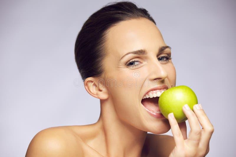 Молодая счастливая женщина есть зеленое яблоко стоковое изображение