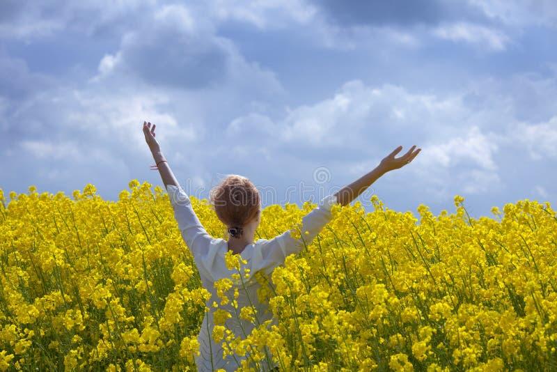 Молодая счастливая женщина идет в канола поле стоковые изображения rf