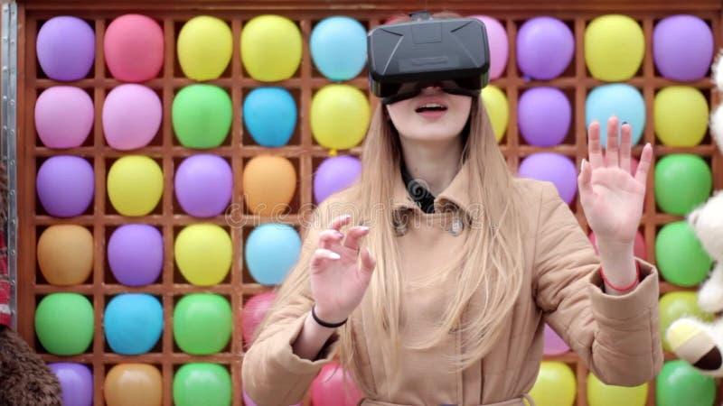 Молодая счастливая женщина на улице в бежевом пальто играя имеющ предпосылку стекел шлемофона виртуальной реальности потехи нося  сток-видео