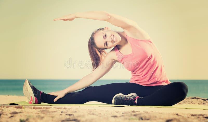 Молодая счастливая женщина работая на циновке тренировки внешней стоковое изображение