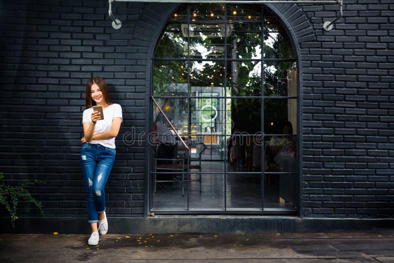 Молодая счастливая женщина стоящая вне кофейни используя ее телефон стоковые фотографии rf
