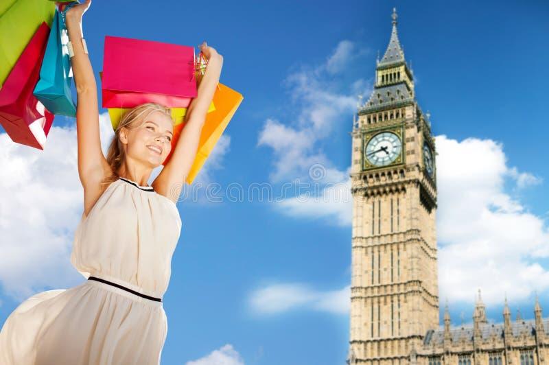 Молодая счастливая женщина с хозяйственными сумками над большим ben стоковые фото