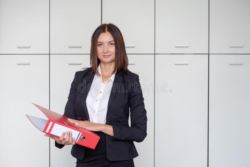 Молодая счастливая коммерсантка держа красную папку и представляя для портрета на офисе, усмехаясь стоковое фото