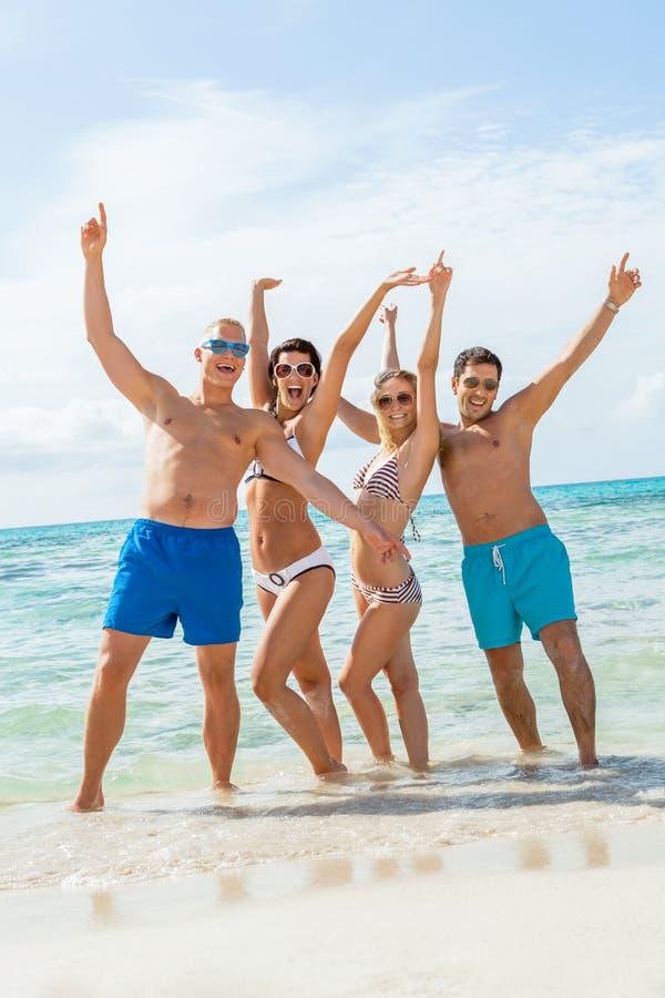 Download Молодая счастливая потеха Havin друзей на пляже Стоковое Фото - изображение насчитывающей рай, кавказско: 37928086