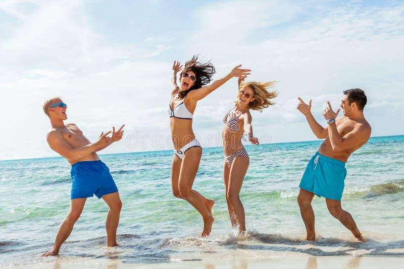 Download Молодая счастливая потеха Havin друзей на пляже Стоковое Фото - изображение насчитывающей приятельство, adulteration: 37928170