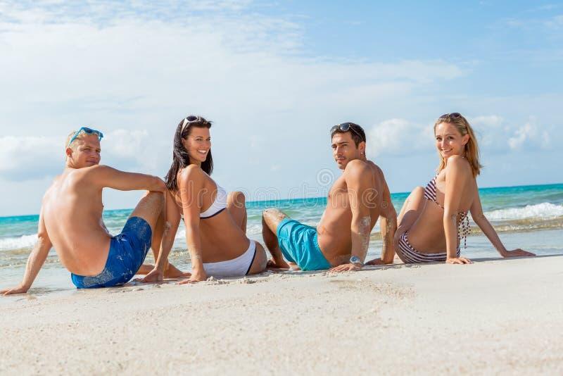 Download Молодая счастливая потеха Havin друзей на пляже Стоковое Фото - изображение насчитывающей красивейшее, праздники: 37928394