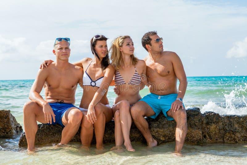 Download Молодая счастливая потеха Havin друзей на пляже Стоковое Изображение - изображение насчитывающей счастье, остров: 37928499