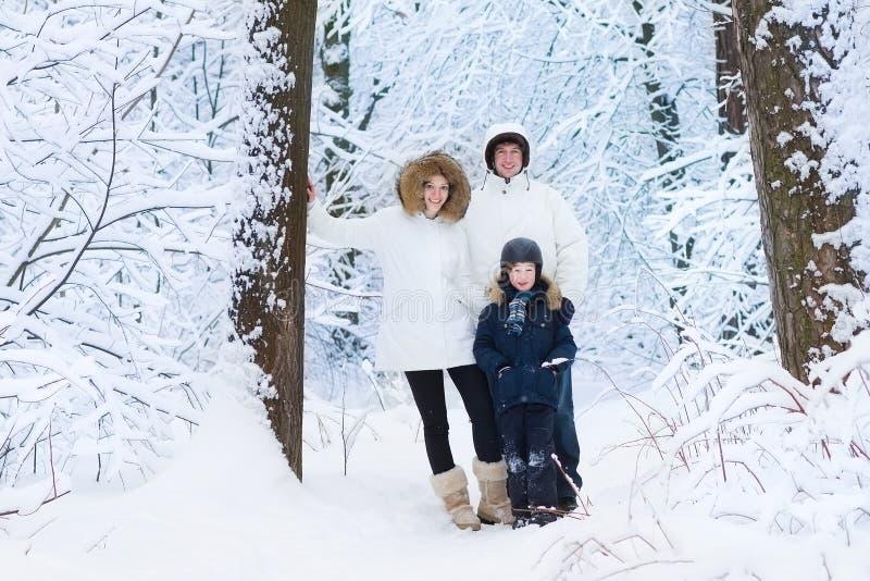 Молодая счастливая семья при сын идя в снежный парк стоковые изображения rf