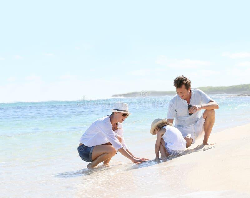 Молодая счастливая семья тратя время на пляже стоковое изображение rf