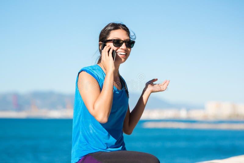Молодая счастливая спортсменка говоря на передвижном снаружи стоковая фотография rf